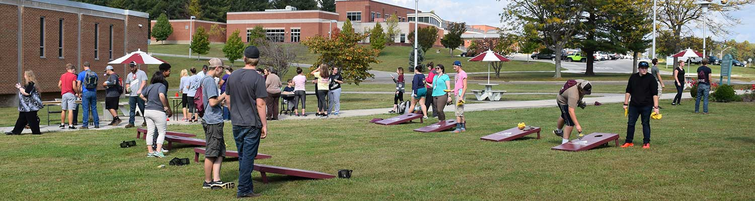 Students playing cornhole on campus