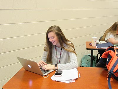 Smiling female student using laptop