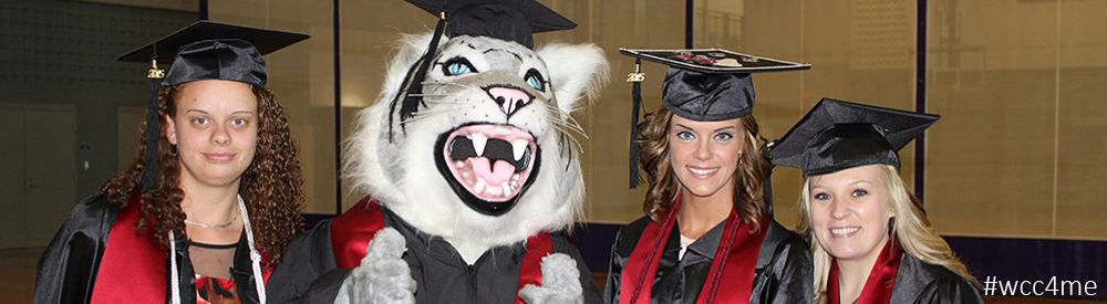 Three WCC graduates with Vic the Wildcat mascot