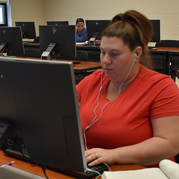 Female Student in computer lab wearing headphones with student on computer in background