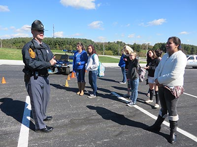 Police Officer Talking to Students in a parking lot
