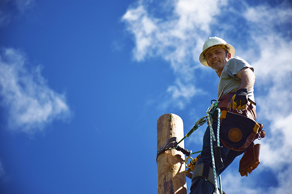 Powerline worker with blue sky background