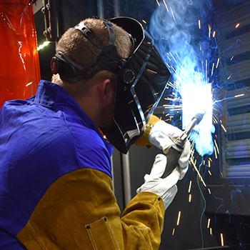 Male student welding with sparks spraying up and down